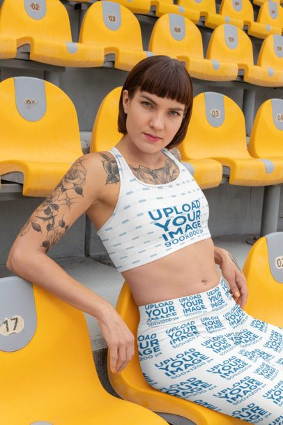 Mockup of a Tattooed Woman in a Stadium Seat Wearing a Sports Bra and Leggings 28725