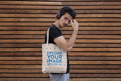 Tote Bag Mockup Featuring a Man With Headphones Against a Wooden Surface 28851