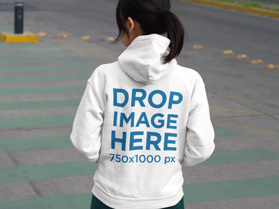 Mockup of the Back of a Girl Wearing a Hoodie While Crossing the Street a9441-b