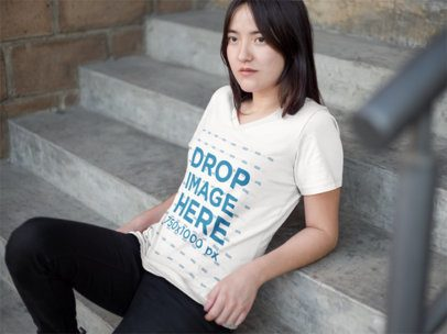 V-Neck T-Shirt Mockup of an Asian Woman Sitting on a Stairway 9536