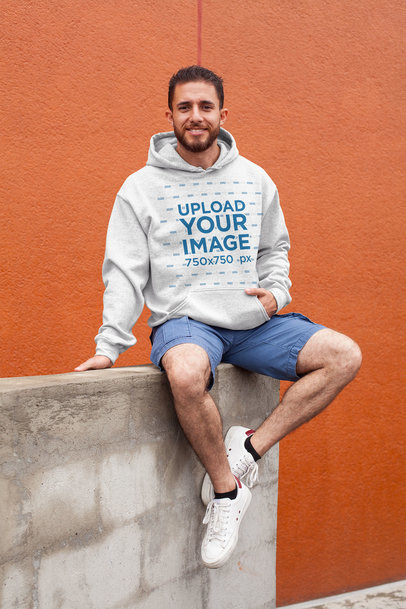 Heathered Pullover Hoodie Mockup Featuring a Smiling Man Sitting on a Wall 28626