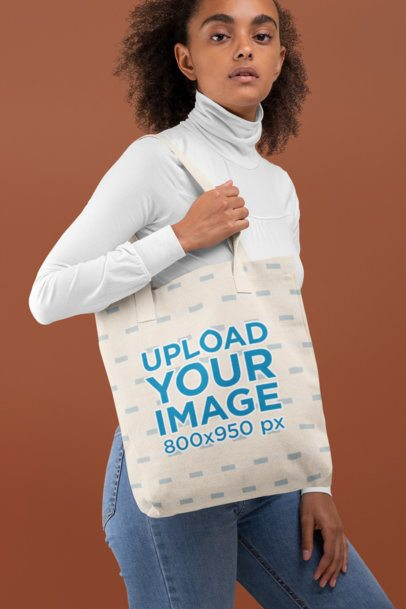 Tote Bag Mockup of a Woman With Curly Hair Against a Plain Backdrop 28869