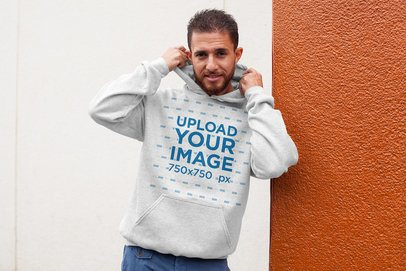 Heathered Hoodie Pullover Mockup of a Man Leaning on a Bicolor Wall 28627