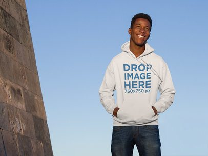 Hoodie Mockup of Guy Standing Next to a Monument a9285