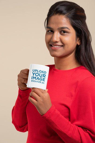 Mockup of a Woman Holding an 11 oz Coffee Mug at a Studio 29079