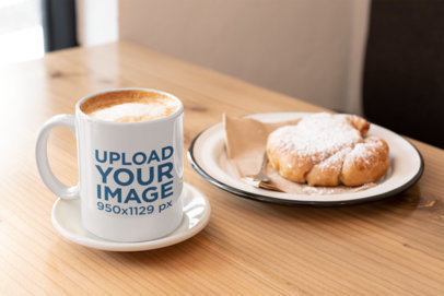 Mockup of an 11 oz Coffee Mug by a Croissant over a Wooden Table 29088
