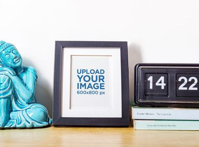Mockup of a Photo Frame on a Table with a Buddha Statue 588-el
