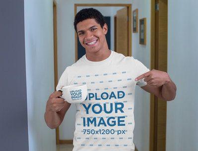 Mockup of a Young Man with a T-Shirt Pointing at a 24 oz Mug 29253