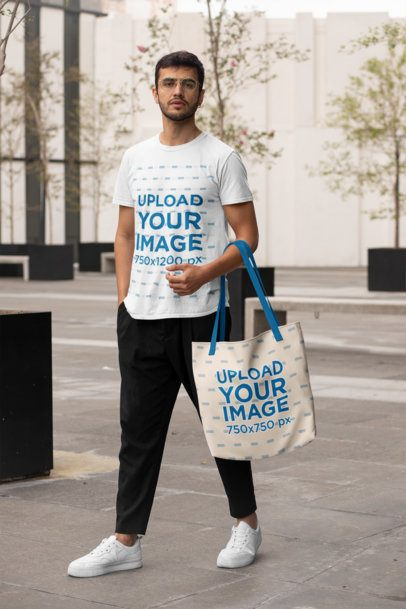 T-Shirt Mockup of a Man with a Customizable Strap Tote Bag Walking in the Street 29408