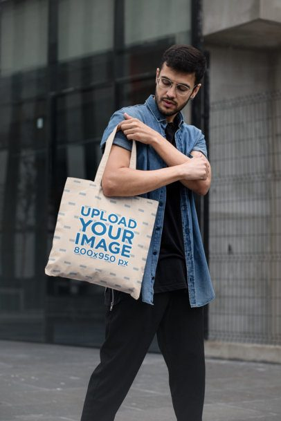 Tote Bag Mockup Featuring a Stylish Man Walking by a Modern Building 29426