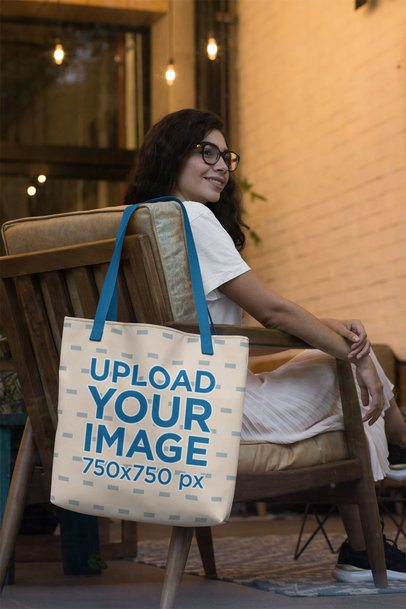 Tote Bag Mockup Featuring a Woman with Glasses Sitting on a Chair 29423