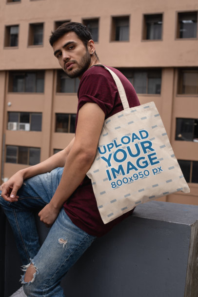 Tote Bag Mockup of a Stylish Man Sitting on a Concrete Fence 29431