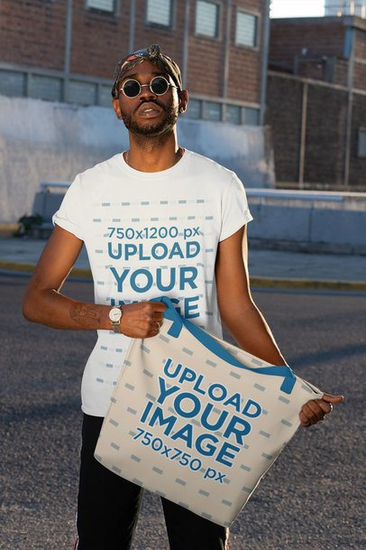 T-Shirt Mockup of a Man Holding a Tote Bag with Customizable Strap 29434