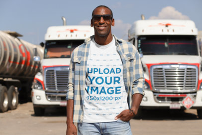 T-Shirt Mockup of a Truck Driver Posing in Front of Two Trucks 29460