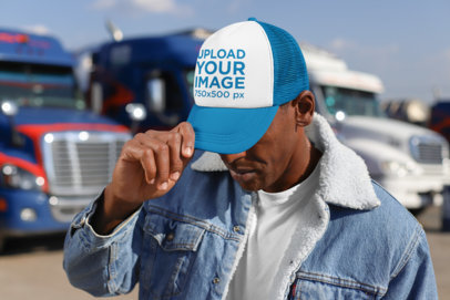Mockup of a Man Covering His Face with a Trucker Hat 29470