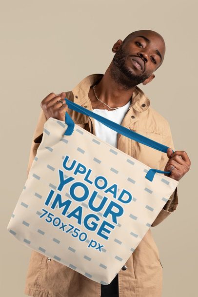 Mockup of a Bald Man Holding a Tote Bag with Customizable Strap at a Studio 29441