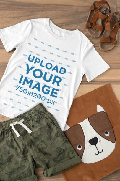 Mockup of a T-Shirt for a Boy Placed on a Wooden Surface with an Outfit 29813