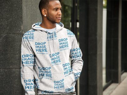 Mockup Template of a Black Man in a Hoodie Leaning Against a Wall a9324