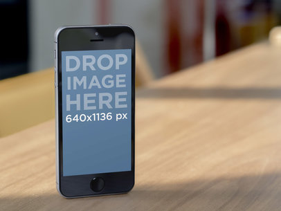 Mockup of a Dark Color iPhone 5 in Portrait Position on a Wooden Table