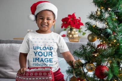 T-Shirt Mockup of a Kid Holding an Ugly Christmas Cushion 30363