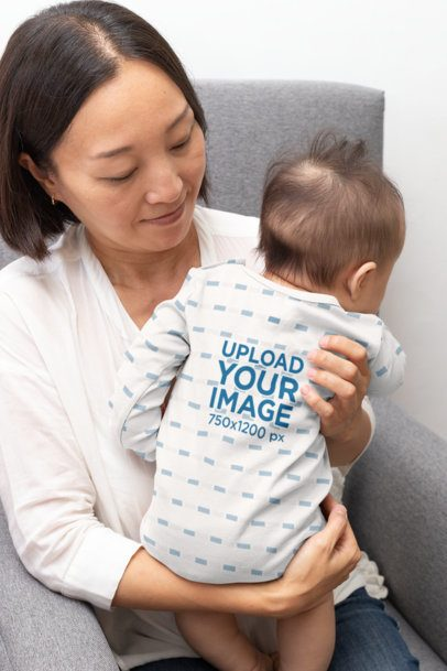 Mockup of a Baby Wearing a Sublimated Onesie in His Mom's Arms 30011