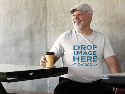 T-Shirt Mockup of an Elder Man Sitting in an Outside Space a8530