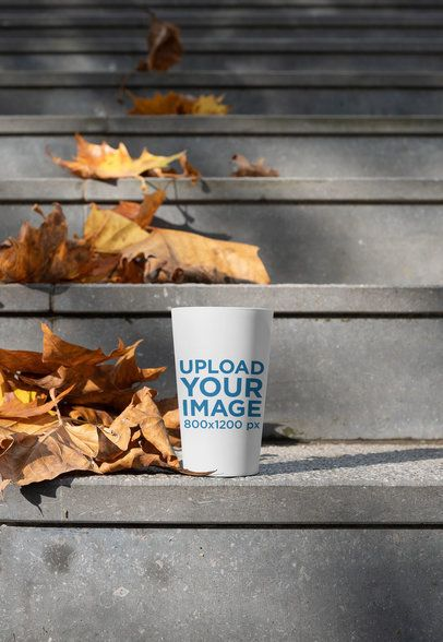Reusable Cup Mockup Featuring a Concrete Staircase and Autumn Leaves 30555
