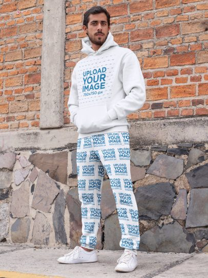 Pullover Hoodie Mockup Featuring a Man with Sweatpants by a Brick Wall 29847