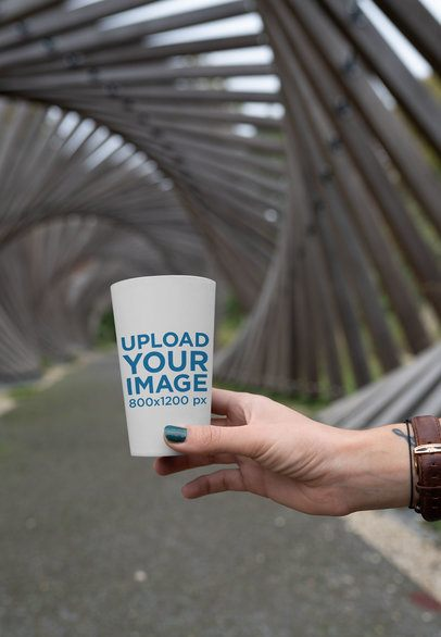 Mockup of a Woman Holding a Reusable Cup Against a Metal Structure 30568