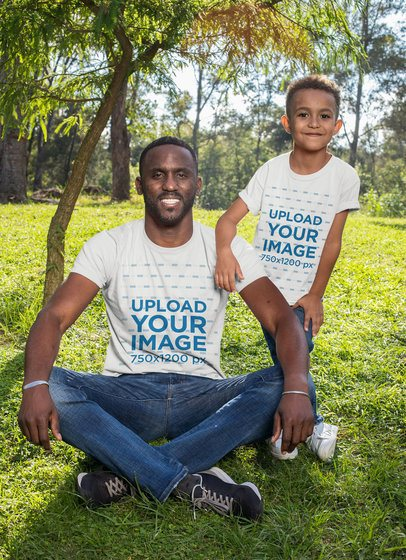 T-Shirt Mockup of a Man Sitting at the Park with His Kid 30595