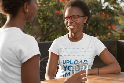 T-Shirt Mockup Featuring a Mother and Daughter Talking at a Table