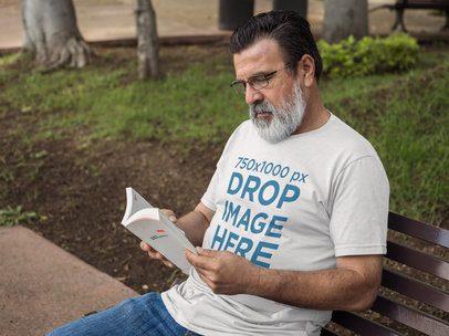 Hispanic Senior Wearing a T-Shirt While Reading Outdoors Mockup a11314