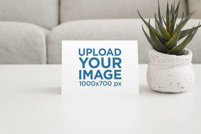 Mockup of a Postcard on a Living Room Table with a Desert Plant 946-el