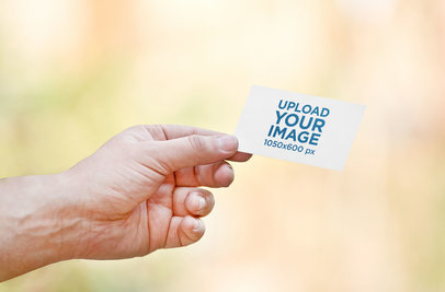 Mockup of a Man Holding a Business Card 1650-el