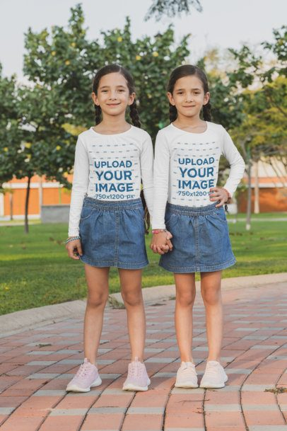 Mockup of Two Sisters With Long Sleeve Tees Holding Hands at a Park 30701
