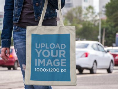 Mockup of a Canvas Tote Bag Mockup Carried by a Woman in the Street a11496