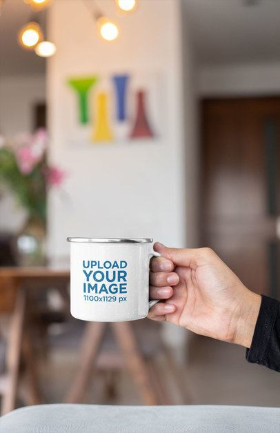 Mockup of a Hand Holding a 12 oz Silver Rim Enamel Mug at a Living Room 30846