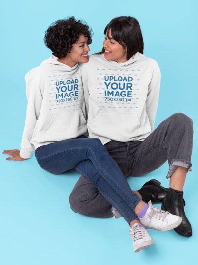 Pullover Hoodie Mockup of a Couple Sitting in a Studio 30400