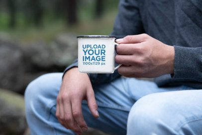 Mockup of a Man Holding a 12 oz Silver Rim Enamel Mug in the Forest 30821