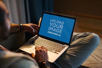 Mockup of a Man Using a MacBook in a Cozy Living Room 2324-el1