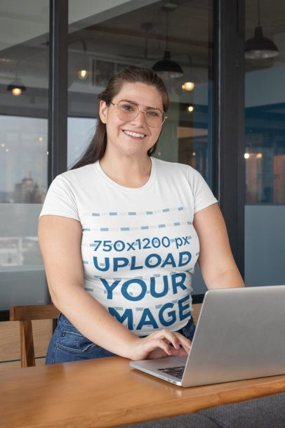 Plus Size T-Shirt Mockup of a Smiling Woman Wearing Glasses while Using Her Laptop 30894