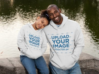 Mockup of a Dad and a Daughter Wearing a Hoodie by the Lake 31397