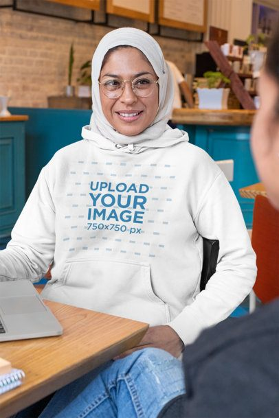 Mockup of a Woman with a Hijab Wearing a Pullover Hoodie at a Café 32083