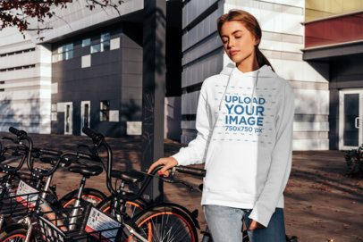 Mockup of a Woman with a Hoodie Posing by a Bike Station 2824-el1