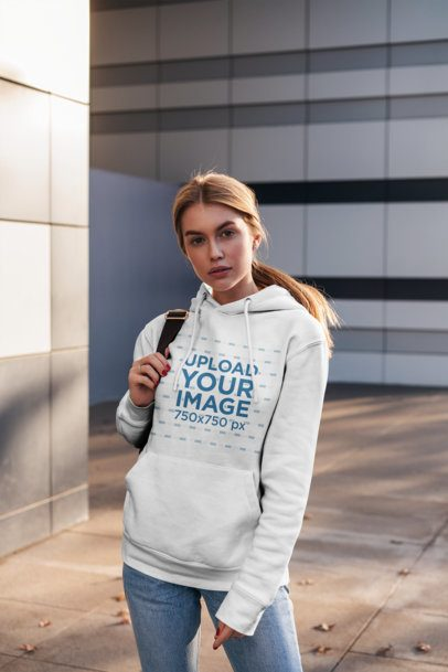 Mockup Featuring a Woman Wearing a Customizable Hoodie and Posing by Modern Buildings 2826-el1