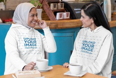 Pullover Hoodie Mockup Featuring Two Joyful Women Chatting at a Coffee Shop 32075
