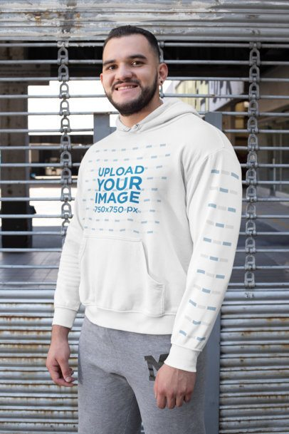 Mockup of a Man Wearing a Pullover Hoodie with a Customizable Sleeve Against a Metal Fence 31484