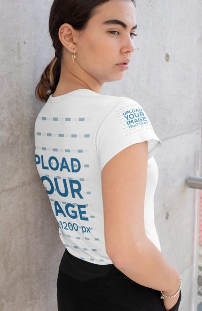 Back View Mockup of a Woman Wearing a T-Shirt with a Customizable Sleeve Against a Wall 31462