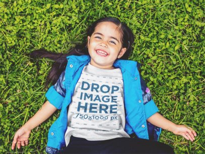 T-Shirt Mockup of a Little Girl Lying in the Grass Smiling a12099