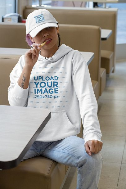 Hoodie Mockup of a Woman Wearing a Dad Hat at a Diner 31188